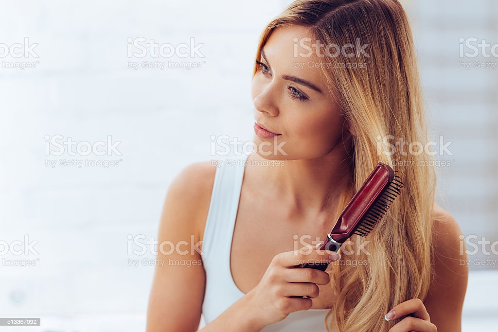 Combing her hair to keep it healthy. stock photo