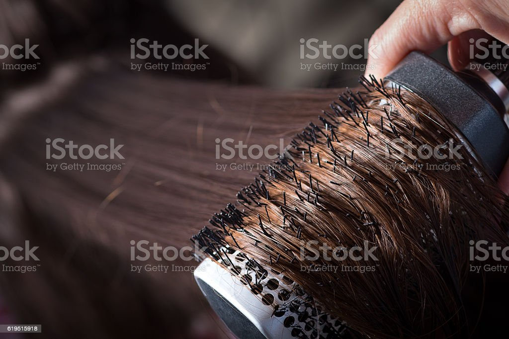 Combing with brush and pulls long hair stock photo