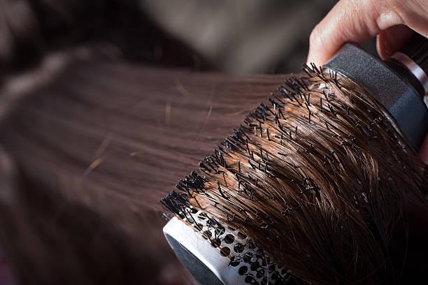 combing with brush and pulls long hair - frisuren für schulterlanges haar stock-fotos und bilder