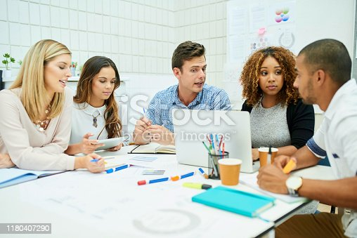 Shot of a group of young designers having a meeting together in their office