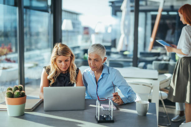 Combining their creative powers Two businesswoman having a meeting in the office age contrast stock pictures, royalty-free photos & images