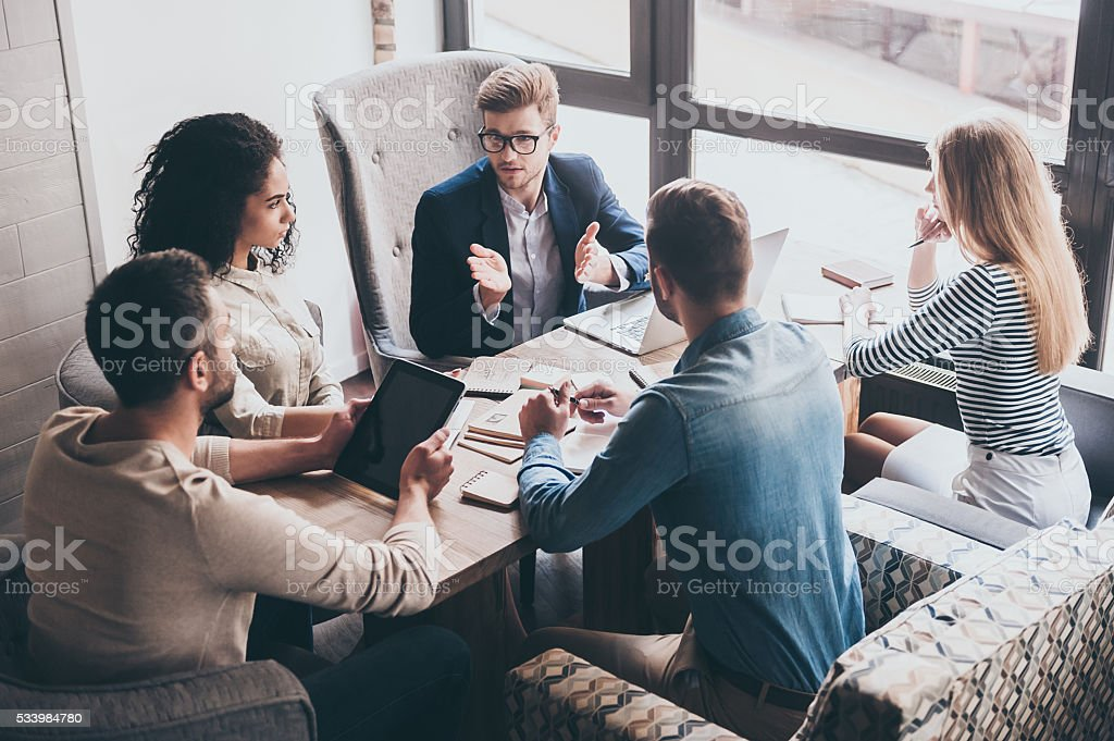 Combining their expertise. Young handsome man in glasses gesturing and discussing something with his coworkers while sitting at the office table Adult Stock Photo