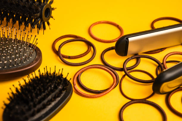 Combs and hairdresser tools in beauty salon work desk on yellow background top view space for text, scrunchy stock photo