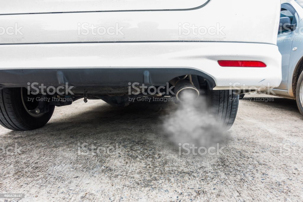 Combustion fumes coming out of car exhaust pipe, air pollution concept. Стоковые фото Стоковая фотография