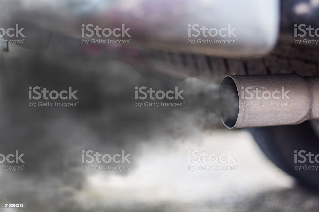 combustion fumes coming out of car exhaust pipe - foto de stock
