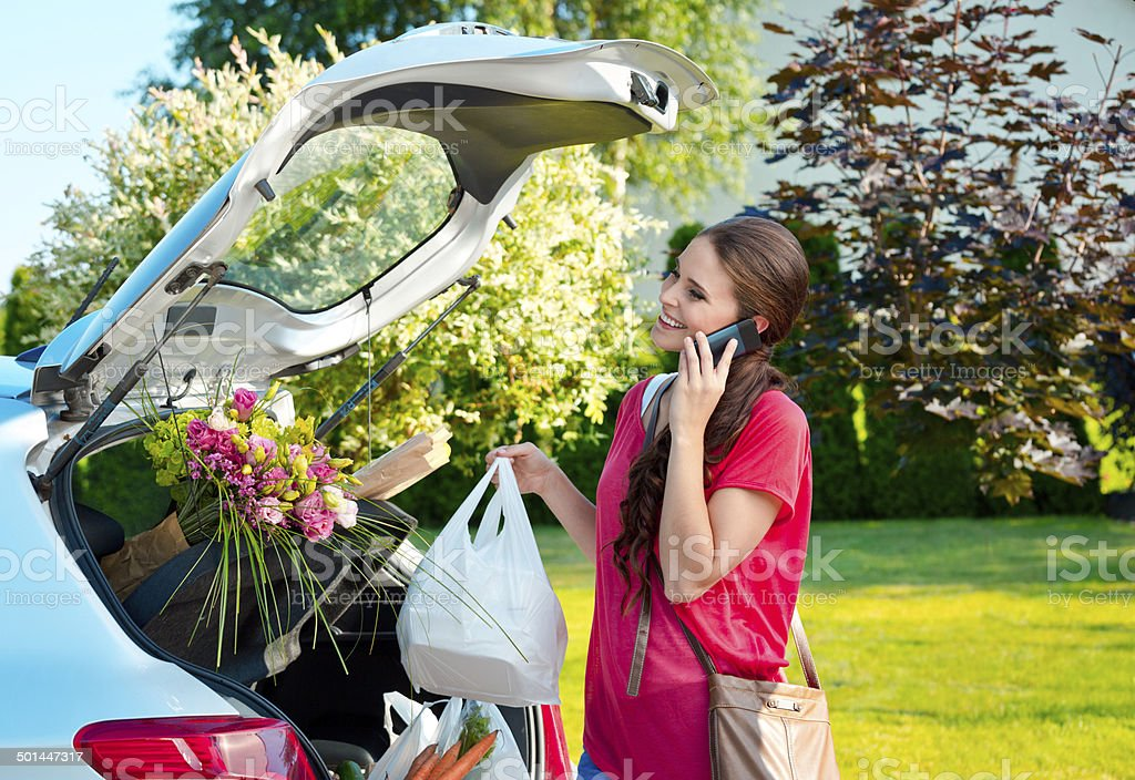 Come back from shopping Young woman taking out the car trunk the groceries, talking on phone. Adult Stock Photo