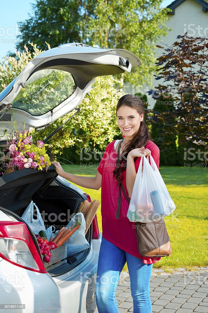 Come back from shopping Young woman taking out the car trunk the groceries, smiling at camera. Adult Stock Photo