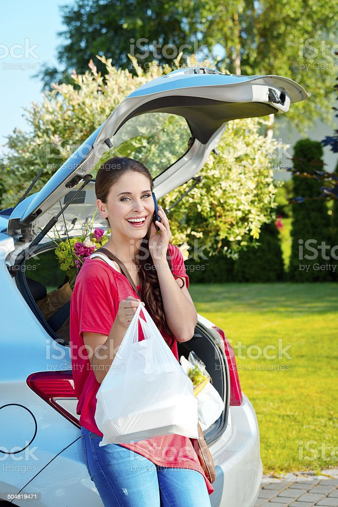 Come back from shopping Cheerful young woman taking out the car trunk the groceries, talking on phone. Adult Stock Photo