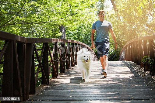 Shot of a handsome young man walking his dog in the park