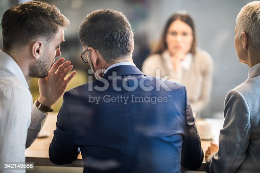 Male member of human resource team whispering to his colleague during a job interview in the office. The view is through glass.