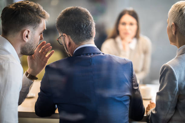 Come closer, what do you think about this candidate? Male member of human resource team whispering to his colleague during a job interview in the office. The view is through glass. privacy stock pictures, royalty-free photos & images