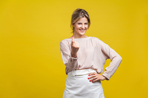 istock Come here! Portrait of playful happy young woman with fair hair in casual beige blouse, isolated on yellow background 1185465991