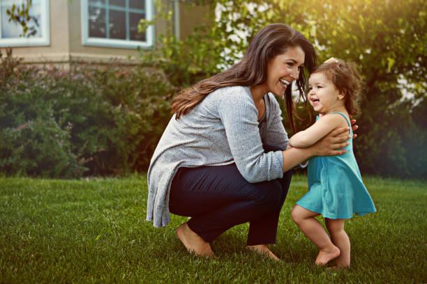 come here, you little bundle of cuteness! - mãe criança brincar relva efeito de refração de luz imagens e fotografias de stock