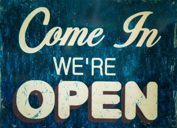 come in we are open sign hanging on a window door stock photo