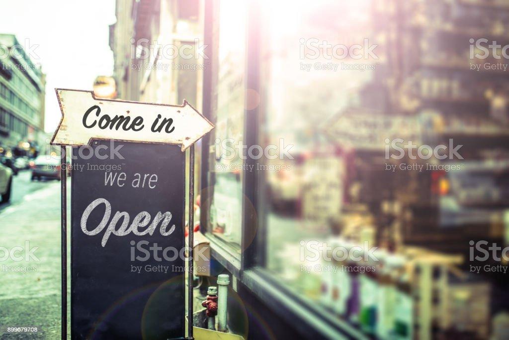 Venga, estamos señal de abierto en una puerta de vidrio - foto de stock