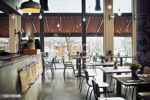 Shot of an empty restaurant filled with tables and chairs inside during the day