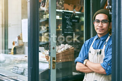 Cropped portrait of a handsome young male shopkeeper standing with his arms folded in the doorway of his self owned deli