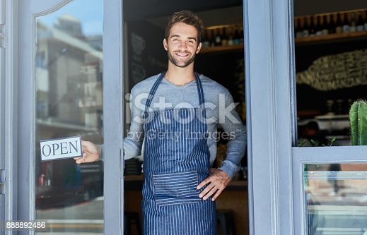 Shot of a handsome young man hanging an open sign in the window of his business