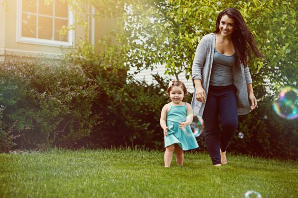 come on mom, we've got so many bubbles to catch! - mãe criança brincar relva efeito de refração de luz imagens e fotografias de stock