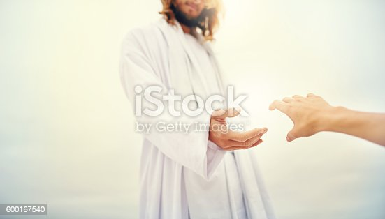 Shot of Jesus standing with his hand outstretched toward a follower on a bare landscape