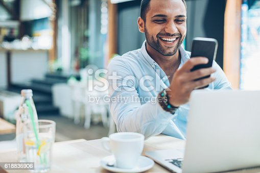 Smiling young man sitting in cafe and checking messages, with his laptop in front of him.