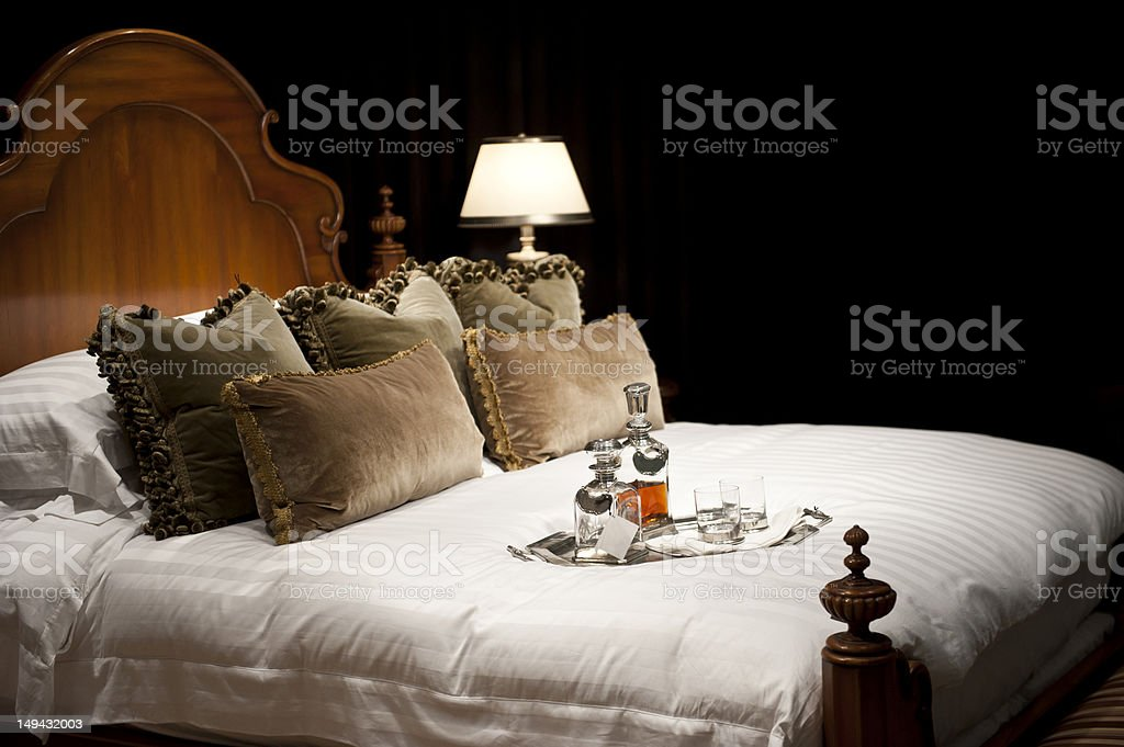 comfortable bed with bottles of alcohol stock photo