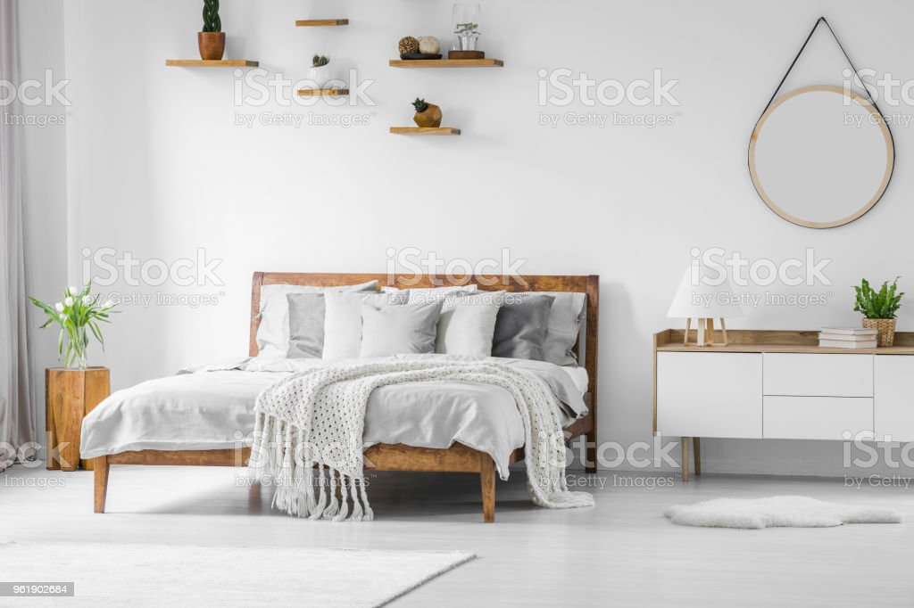 Comfortable big wooden framed bed with linen, pillows and blanket, nightstand beside and round mirror hanging on a white wall in a bright bedroom interior. Real photo. royalty-free stock photo