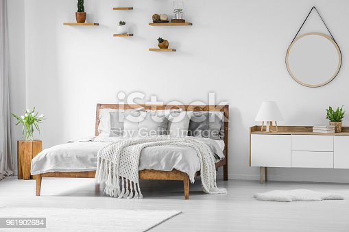 Comfortable, big, wooden bed with linen, pillows and blanket, nightstand beside and round mirror hanging on a white wall in a bright bedroom interior. Real photo.