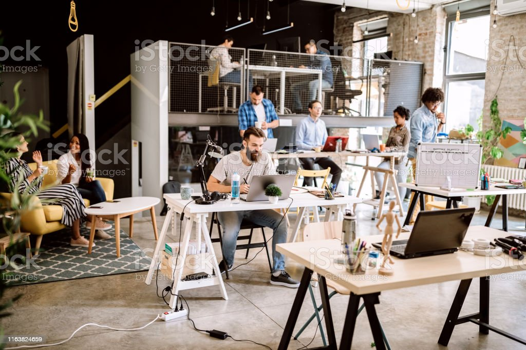 Comfortable co-working space, some coworkers arriving at work Satisfied Freelance Workers Working Together in Coworking Space 25-29 Years Stock Photo