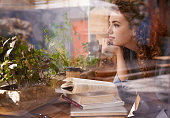 An attractive young woman sitting with her books in a coffee shop