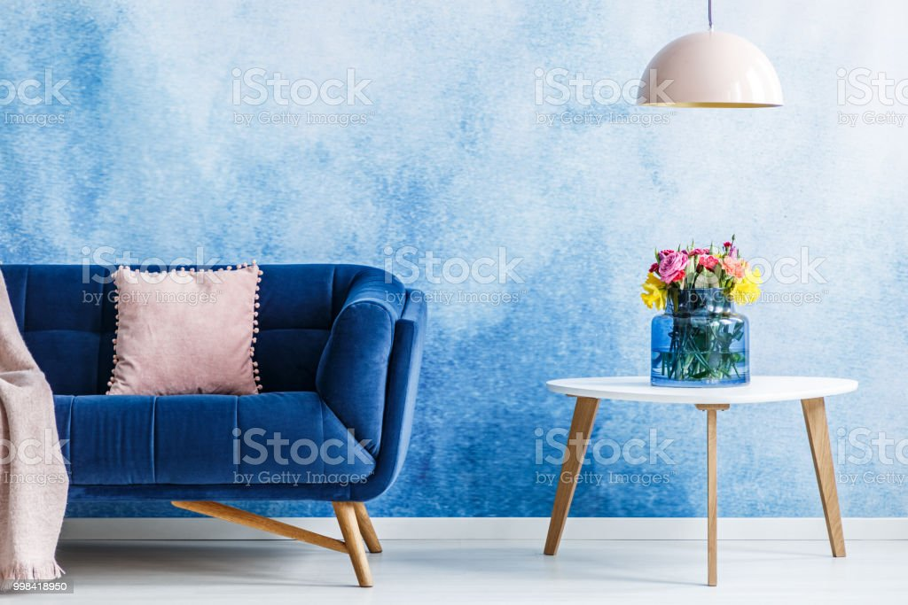 Comfortable Plush Settee With Pastel Cushion And A Side Table With Fresh  Flowers In A Vase