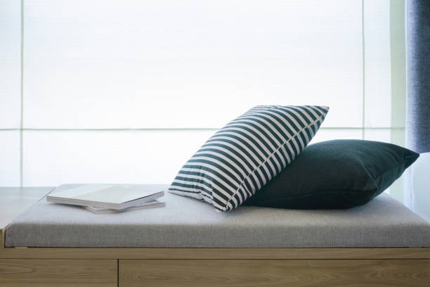 Comfortable seat next to window with pillows and books Comfortable seat next to window with pillows and books chaise longue stock pictures, royalty-free photos & images