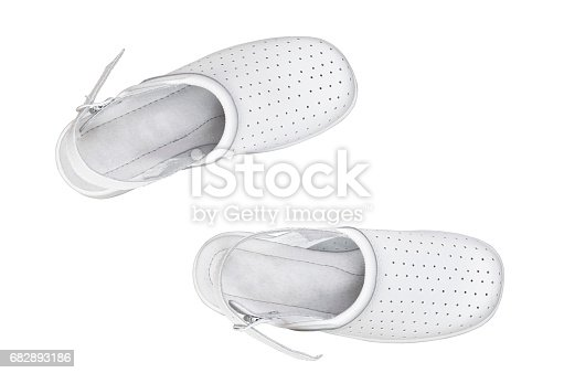 a pair of white comfortable shoes. Clogs isolated over white.