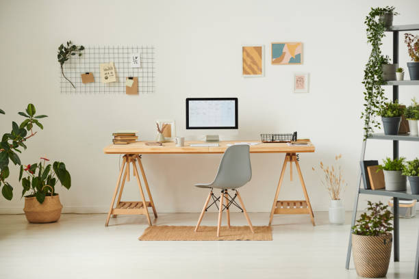 comfortable workplace with potted plants, wall organizer, pictures and computer - estudio imagens e fotografias de stock