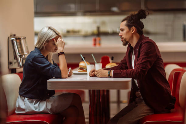 Comforting her Young couple breaking up while having dinner in a restaurant brekeup stock pictures, royalty-free photos & images