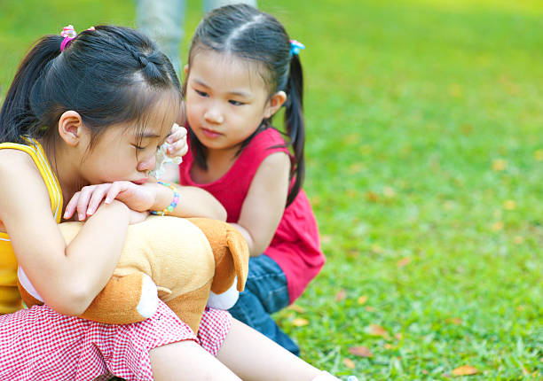 comforting Little girl is comforting her crying sister apologist stock pictures, royalty-free photos & images
