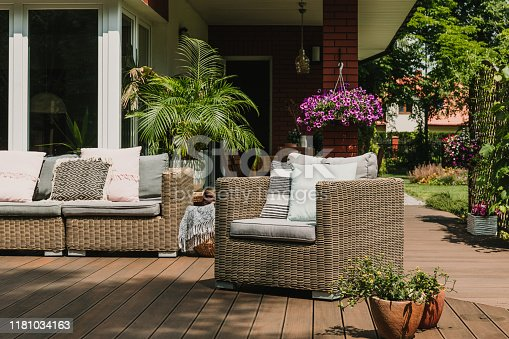 istock Comfy wicker armchair with pillows on wooden terrace of trendy suburban home 1181034163