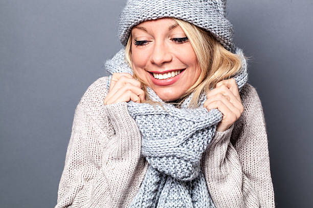 comfy young beautiful blond woman smiling with sexy winter scarf - wollschal stock-fotos und bilder