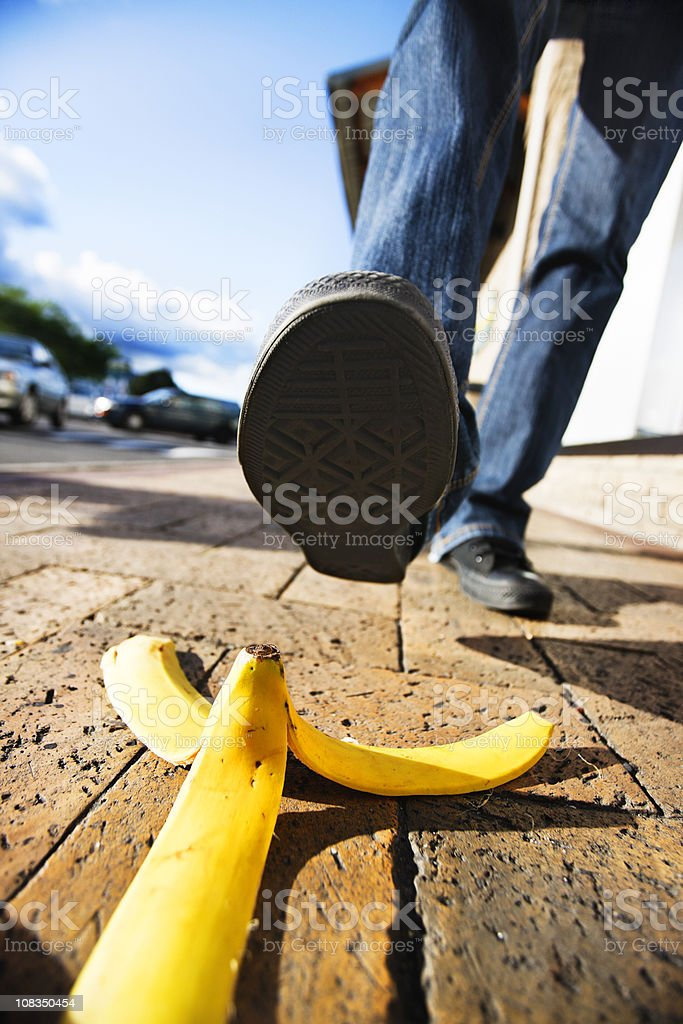Comic accident classic about to happen: foot approaches banana peel stock photo
