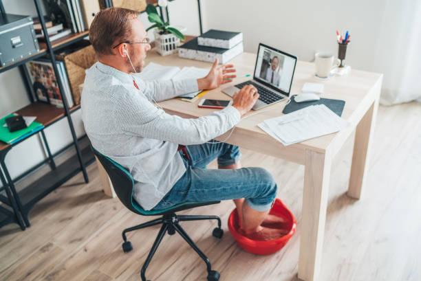 Situación de la oficina en casa moderna cómica. Hombre de negocios tienen una videollamada charlando en la computadora portátil y elevando sus pies en Foot Hot Bath debajo de la mesa. Trabajo a distancia en la imagen del concepto de tiempo de cuarentena - foto de stock