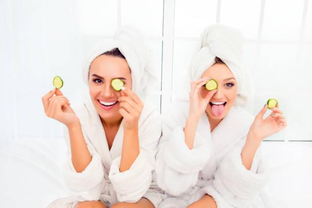 comic-jungen schwestern nach dusche machen maske mit gurke - gurkenmaske stock-fotos und bilder