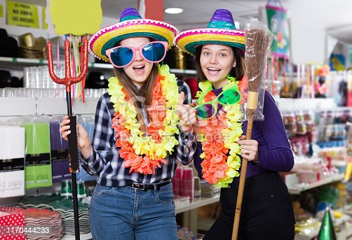 Comically dressed young women joking while visiting festive accessories store