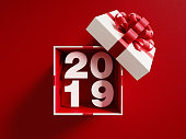 2019  is coming out of a white gift box tied with red ribbon on red background. Horizontal composition with copy space. Directly above. Great use for Christmas related gift concepts.