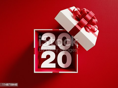 2020 is coming out of a white gift box tied with red ribbon on red background. Horizontal composition with copy space. Directly above. Great use for Christmas related gift concepts.