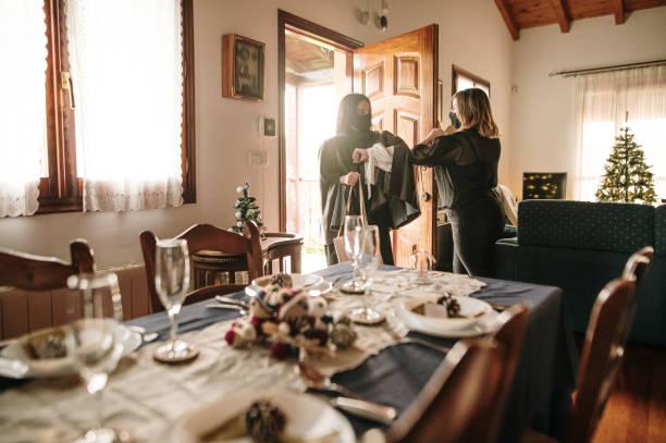 nadchodzi na kolację bożonarodzeniową podczas pandemii covid-19 - kolacja spotkanie towarzyskie zdjęcia i obrazy z banku zdjęć