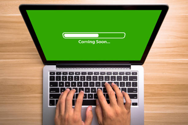 Coming soon Concept Laptop Screen With Typing Hands On Keyboard stock photo