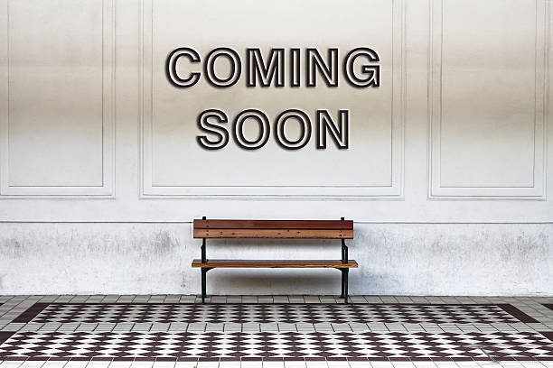 Coming soon concept Coming soon written on a wall above a wooden bench - concept image absentee stock pictures, royalty-free photos & images