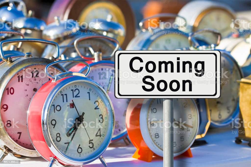 Coming soon sign - concept image with old colored metal table clocks stock photo