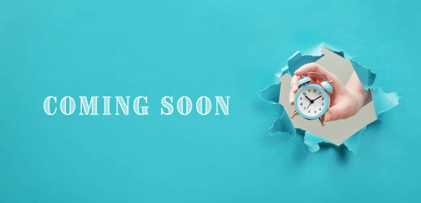 Coming Soon text on blue background. Alarm clock in hand. Concept of announcement, opening stock photo