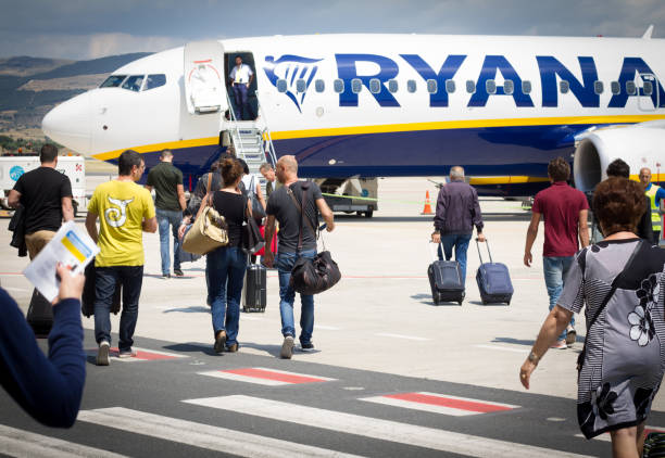 Comiso, Sicily, Italy: Passengers Boarding Ryanair on Tarmac Comiso, Sicily, Italy: Passengers on the tarmac at Comiso Airport in Sicily walking with carry-on luggage toward a Ryanair airplane. Comiso is in Ragusa Province, in the Southeast part of Sicily. carry on luggage stock pictures, royalty-free photos & images
